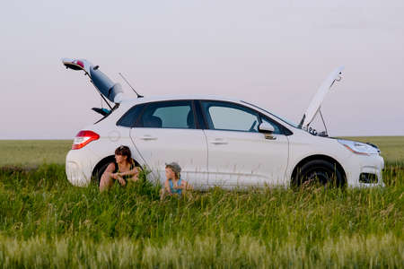 Mom and Son Sitting Beside their White Defective Car While Waiting for a Mechanic Stock Photo