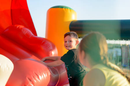 Small blonde boy (6-8 years) wearing t-shirt playing on red bouncy castle looking at camera, rear view of brunette girl (9-10 years) in foreground