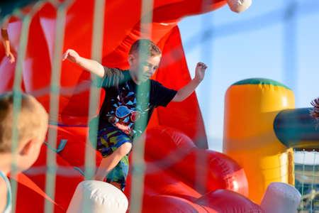 Kleine blonde jongen (6-8 jaar) het dragen van t-shirt en korte broek hard concentreren op het spelen buiten in rood springkasteel, netten en kind zichtbaar op voorgrond Stockfoto
