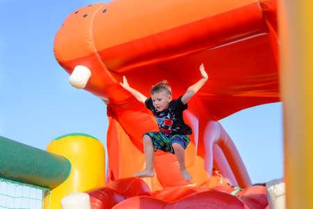 Jonge jongen die op blote voeten op een plastic kasteel springen met zijn armen in de lucht als hij geniet van een zomerse dag op een speelplaats of beurs Stockfoto