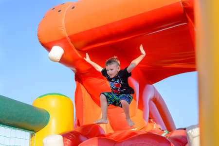barefoot: Young boy jumping barefoot on a plastic jumping castle with his arms in the air as he enjoys a summer day at a playground or fair