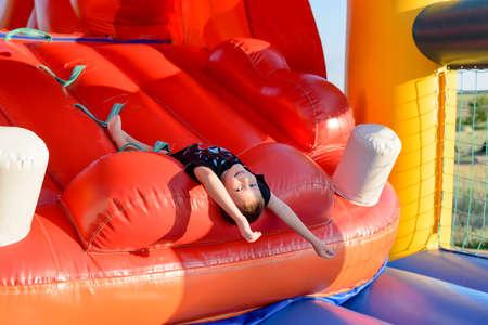 Smiling boy (7-9 years) wearing black t-shirt lies upside down on slide of red bouncy castle