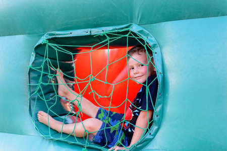 little boys: Full length of small blonde boy (6-8 years) wearing t-shirt and shorts in his bare feet sitting in blue netted window of bouncy castle, looking at camera