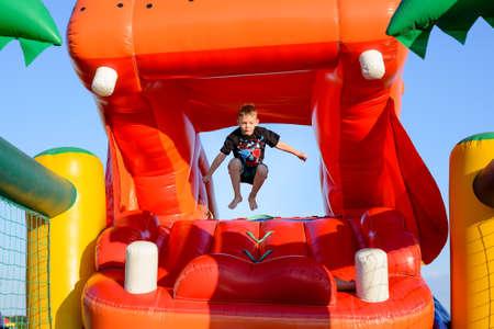 niño saltando: Pequeño muchacho (6-8 años) vistiendo la camiseta y pantalones cortos de saltar pie desnudo en el aire en un castillo hinchable colorido, cielo azul en el fondo