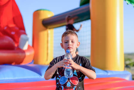 undoing: Young boy drinking bottled water as he stands in front of a colorful plastic jumping castle at a playground or fairground