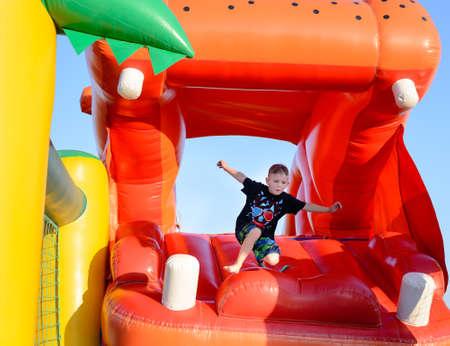 pies descalzos: Muchacho joven que salta descalzo en un castillo inflable de plástico con sus brazos en el aire mientras disfruta de un día de verano en un parque o una feria