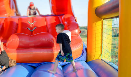 Full length of small boy (6-8 years) wearing t-shirt and multi-colored shorts walking in bare feet across blue base of multi-colored bouncy castle, children in background Archivio Fotografico