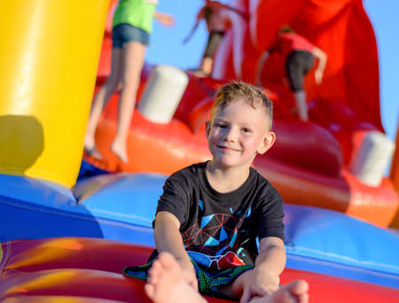opening party: Smiling happy barefoot little boy sitting on a colorful inflatable plastic jumping castle at a fairground or kids playground Stock Photo