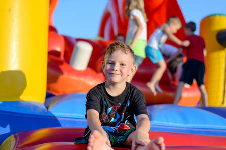 Smiling happy barefoot little boy sitting on a colorful inflatable plastic jumping castle at a fairground or kids playground Foto de archivo