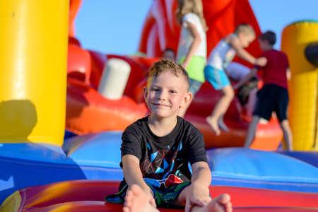 niño saltando: Sonriendo feliz niño pequeño sentado descalzo en un colorido inflable castillo inflable de plástico en un parque de atracciones o parque infantil