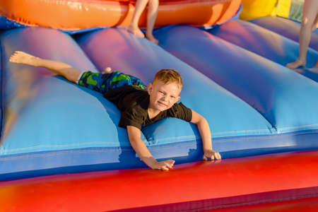 playground equipment: Full length of small blonde boy (6-8 years) wearing black t-shirt and multi-colored shorts lying on blue bouncy castle looking at camera, legs of other children visible in background