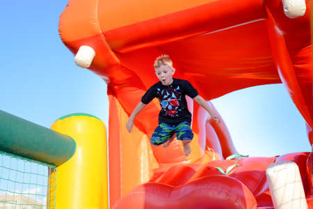 Small boy having fun on a jumping castle leaping in the air as he jumps down from the mouth of a plastic hippo Standard-Bild