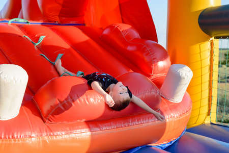 lies down: Smiling boy (7-9 years) wearing black t-shirt lies upside down on slide of red bouncy castle