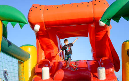 castle: Young Boy Jumping on Bouncy Castle, Having Fun on Inflatable Slide Shaped Like Mouth of Giant Red Hippopotamus Stock Photo