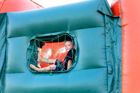 playground equipment: Full length of small blonde boy (6-8 years) wearing t-shirt and shorts in his bare feet sitting in blue netted window of bouncy castle, looking at camera