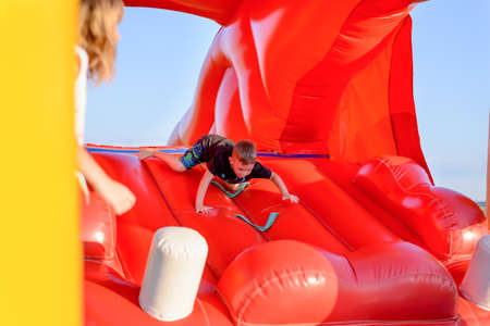 Small boy (7-9 years) wearing black t-shirt and shorts scrambles down slide of bouncy castle, part of blonde girl visible in foreground, blue sky in background