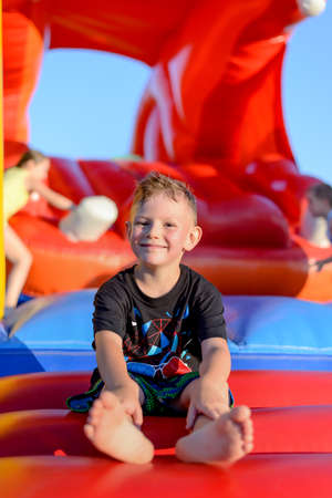 fairground: Smiling happy barefoot little boy sitting on a colorful inflatable plastic jumping castle at a fairground or kids playground Stock Photo
