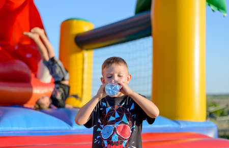 undoing: Thirsty young boy drinking bottled water after playing on colorful plastic equipment at a funfair or childrens playground