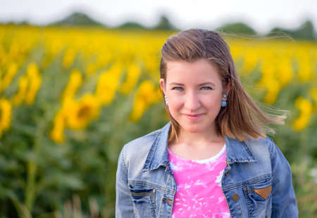 cute teen girl: Close up Pretty Blond Girl Wearing Denim Jacket, Smiling at the Camera Against Blurry Sunflower Field