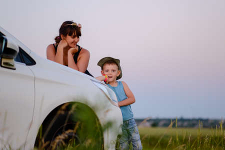 Mother and Son Looking at the Camera While Leaning on the Front of White Car