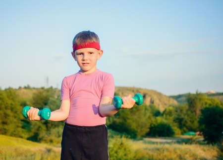 muscle toning: Half Body Shot of an Athletic Cute Boy with Red Warrior Headband, Lifting Two Small Dumbbells and Looking at the Camera Against Green Mountain and Sky. Stock Photo