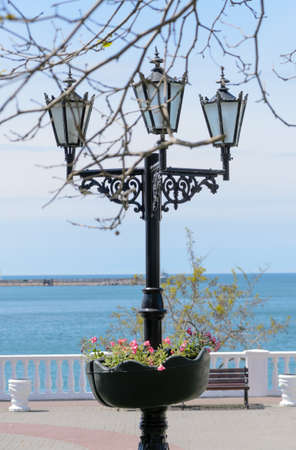 seafront: Ornate wrought iron lamppost with flowers on a coastal esplanade overlooking a calm ocean