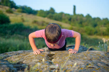 muscle toning: Sporty Young Boy Doing Push up Exercise on Top of a Boulder on a Sunny Day Against Blurry Nature Background.