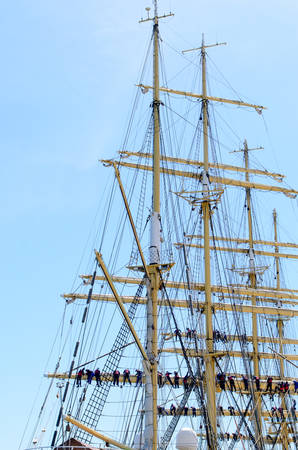 masts: Sailors on the rigging of a tall ship balanced along the yard arm attending to the sails, multiple masts and crew against a blue sky