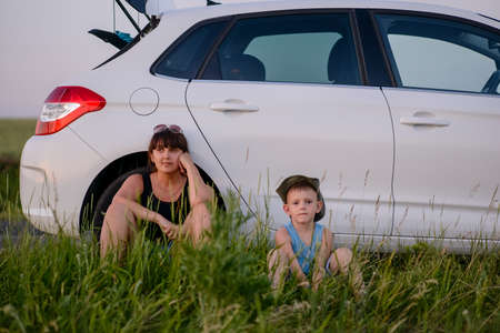 Serious Mom with is Cute Son Sitting Beside their White Car While Waiting for Something.