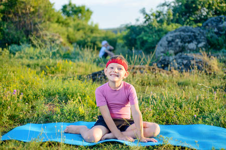 strong boy: Young Boy Wearing Fitness Attire, Siting on Blue Mat at the Green Grasses and Smiling at the Camera. Stock Photo