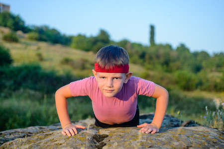 body toning: Sporty Young Boy Doing Push up Exercise on Top of a Boulder on a Sunny Day Against Blurry Nature Background.