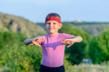 arte marcial: La mitad Shot cuerpo de un Feliz Hombre Kid con Guerrero Diadema Practicar algunos movimientos de artes marciales en el suelo con feliz expresi�n facial.