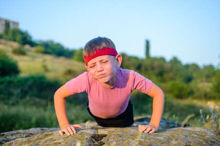 forcing: Athletic Young Boy Forcing his Body to Lift While Doing Push Up Exercise on Top of a Big Rock with Sacrificing Facial Expression.