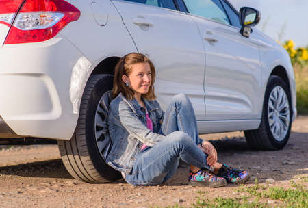 sitting on the ground: Thoughtful Pretty Girl Sitting on the Ground and Leaning her Back Against Vehicle Tire and Looking Into the Distance with Happy Facial Expression.