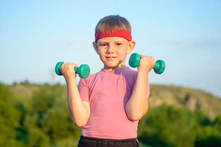 bodybuilding boy: Half Body Shot of an Athletic Cute Boy with Red Warrior Headband, Lifting Two Small Dumbbells and Looking at the Camera Against Green Mountain and Sky. Stock Photo