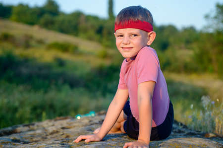 body toning: Athletic Handsome Boy Looking at the Camera While Doing Side Planking Exercise on Top of Boulder at the Field