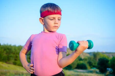 Close up Strong Cute Boy with Red Headband Doing an Outdoor Exercise and Lifting Small Dumbbell Against Blurry Nature Background. Standard-Bild