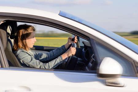 manejando: Conductor joven mujer que conduce un coche blanco en la carretera con Focused Expresión facial.