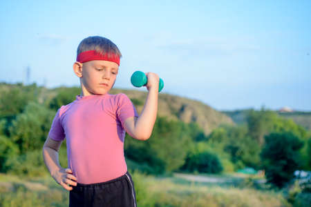 Smiling Strong Cute Boy Lifting Dumbbell with his Right Hand on his Waist While Doing an Outdoor Exercise