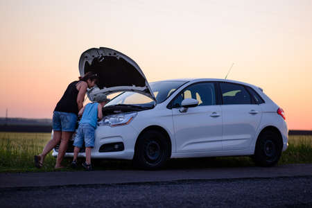 Moeder met zoon op zoek naar de camera tijdens het openen van de voorkant van een defecte auto op de Grassy Ground.