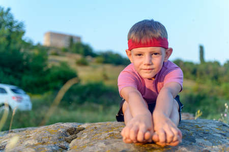 Little boy working out on a rock outdoors doing stretching exercises reaching forwards to touch his toes Stock Photo