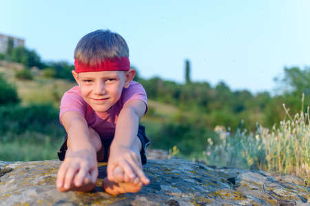 supple: Little boy working out on a rock outdoors doing stretching exercises reaching forwards to touch his toes Stock Photo