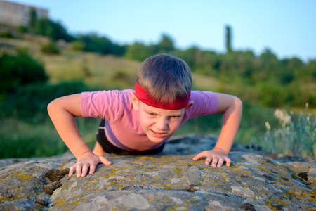 straining: Young boy doing push-ups on a rock outdoors in the countryside as he does his training exercises, frontal view