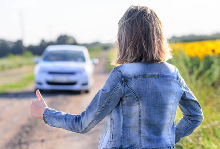 flagging: Woman in denim jacket and jeans standing hitchhiking on a rural dirt road flagging down an approaching car, view from the rear