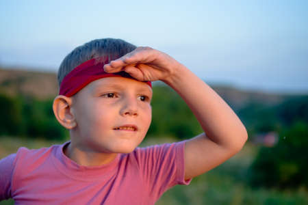 perturbed: Little boy wearing a red headband standing peering into the sunset with his hand raised to his forehead, head and shoulders portrait