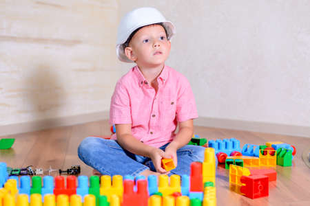 Creative young boy wearing a hardhat sitting on a hardwood floor thinking about what to build with his colorful plastic building blocks
