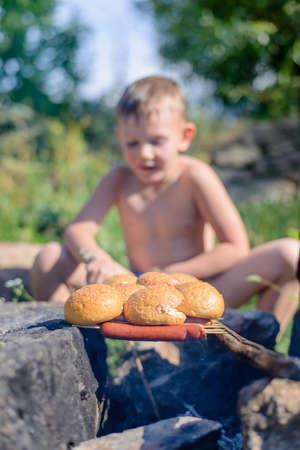 ni�o sin camisa: Sentado Sin camisa muchacho joven que asa a Pan y Salchichas en los palillos para el almuerzo en un d�a muy soleado d�a. Foto de archivo