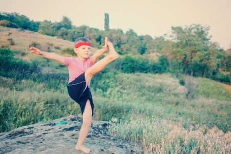 Supple young boy doing exercises standing on a rock in the garden balancing on one leg with the other raised up into the air above his head