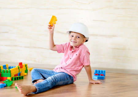 boy sitting: Young boy wearing hardhat playing indoors sitting on a wooden floor grinning as he holds up a large colorful plastic building block