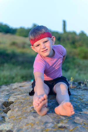 muscle boy: Little boy working out on a rock outdoors doing stretching exercises reaching forwards to touch his toes Stock Photo